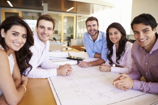 Smiling-workers-at-meeting-table